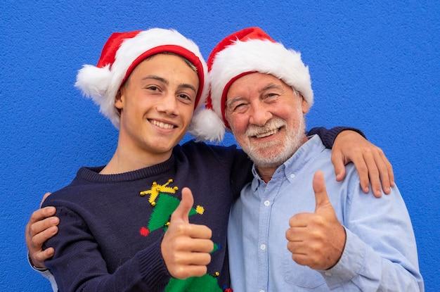 Пара деда с улыбкой внука подростка делает хорошо знаком с руками, носить рождественский свитер и шляпы санта-клауса. концепция семьи, дружбы и веселья