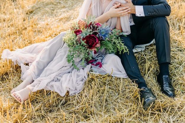 大きな結婚式の花束を保持している新郎と新婦のカップル。