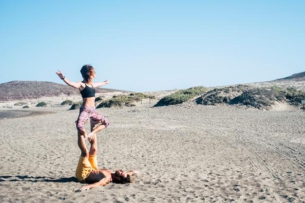 Пара парней, занимающихся акройогой или йогой на пляже в тишине, чтобы сосредоточиться и не упасть - на песке, на песке и камнях на заднем плане