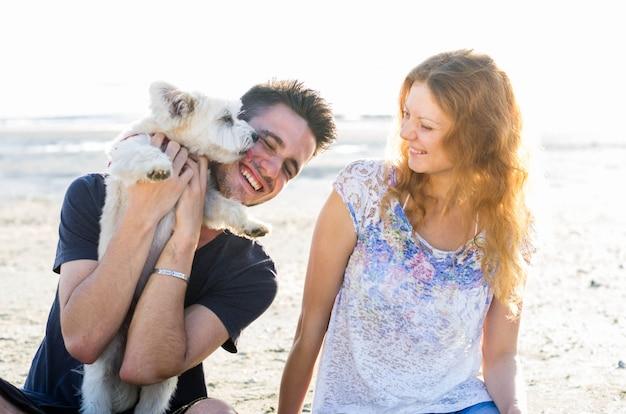 ビーチで犬と遊んでいる男のカップル