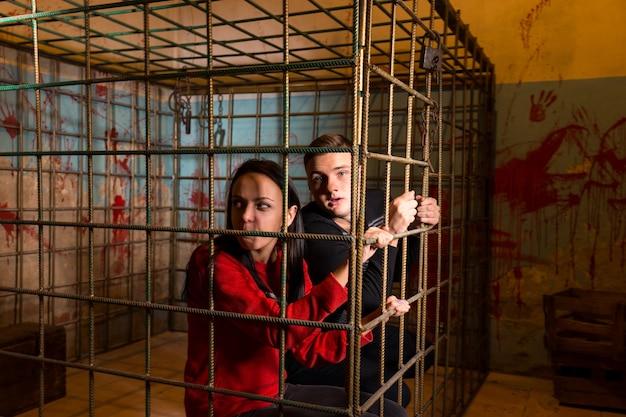 Пара жертв хэллоуина, заключенных в металлическую клетку с забрызганной кровью стеной позади них, выглядывают через решетку