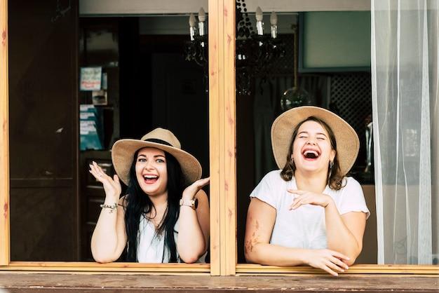 幸せな陽気な若い女の子のカップルが楽しみ、友情の中でたくさん笑う