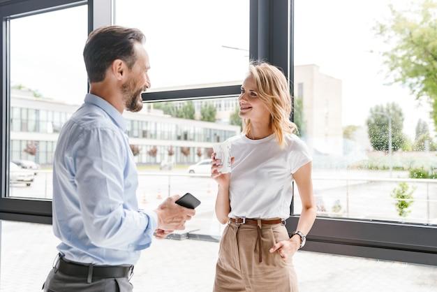 Пара счастливых коллег разговаривает стоя