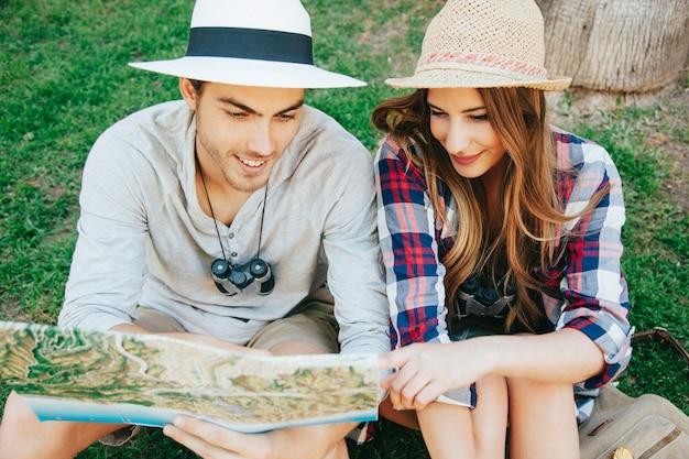 Пара счастливых путешественников на траве