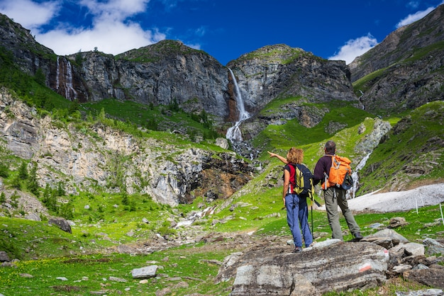 Пара туристов, глядя на водопад на горе