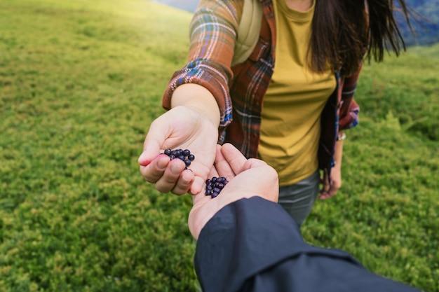 山の頂上で収穫されたブルーベリーを共有するハイカーのカップル健康的なライフスタイルの概念