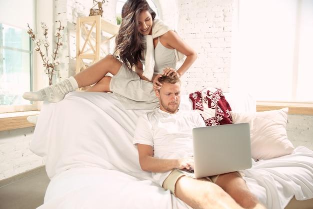 一緒にリラックスして家にいる恋人たちのカップル。週末を過ごしている白人の男性と女性は、優しくて幸せそうに見えます