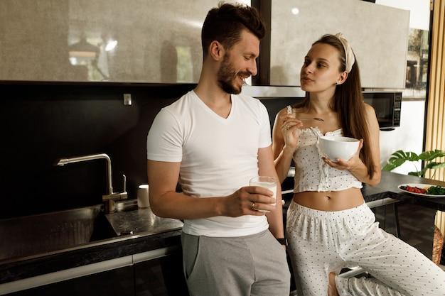 自宅のキッチンで一緒に朝食をとっている恋人のカップル