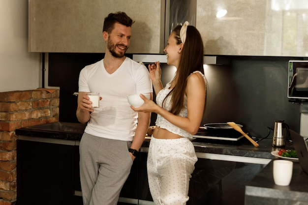 キッチンで一緒に朝食をとり、笑っている恋人たちのカップル