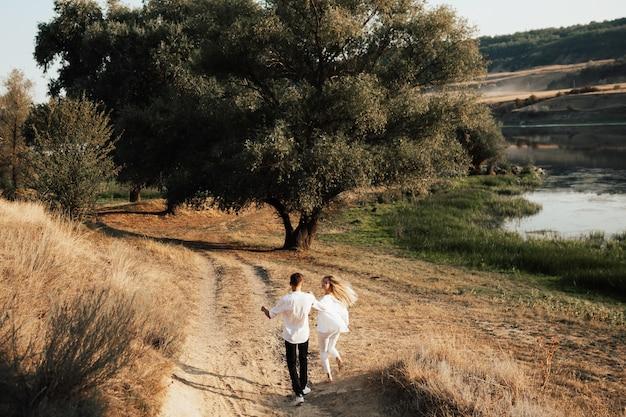 手をつないで走り、公園で楽しんでいる恋人たちのカップル。