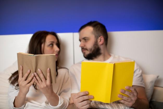 恋人のカップルはお互いを見ながら、ベッドに本を置いています