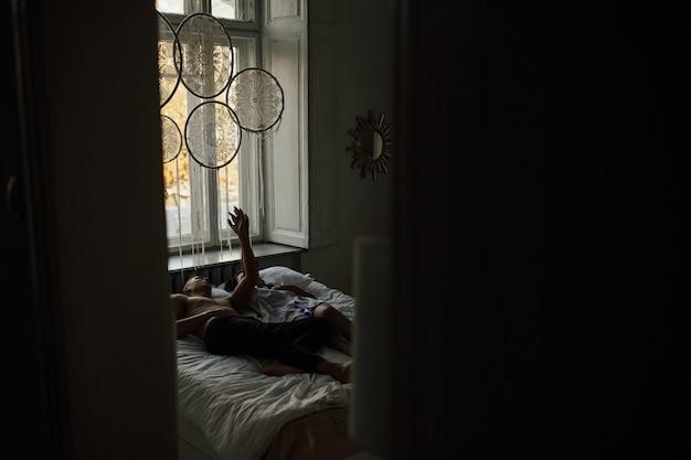 朝のベッドでリラックスした恋人たちのカップル。彼らは手をつないでいます。暗いインテリア。