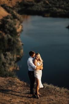 湖のある丘の上で屋外でお互いを愛し合うカップル。恋人のカップルが立って抱きしめています。