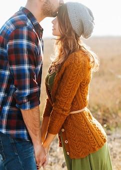 男性と女性のカップルが手をつないで、屋外で、男性が女性の額にキスします。
