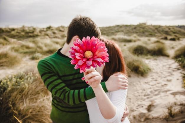 Пара мужчин и женщин, целуя вас, покрытых цветком
