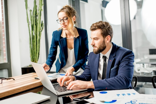 Пара менеджеров в костюмах, работающих вместе с ноутбуком и документами в роскошном офисном интерьере