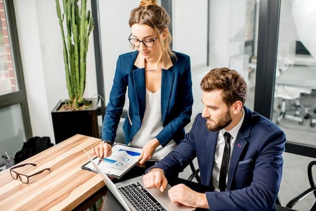 高級オフィスのインテリアでノートパソコンやドキュメントと一緒に働くスーツのマネージャーのカップル