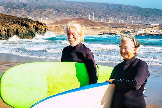 큰 서핑 보드와 함께 해변에서 함께 서핑하는 노인과 노인 또는 노인의 커플. 야외에서 수상 스포츠를 하며 여름을 즐기고 있는 두 노인