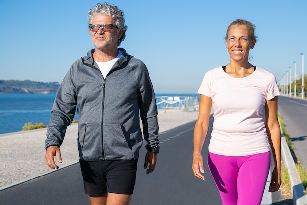아침 실행 후 강둑을 따라 걷는 성숙한 조깅 커플. 전면보기, 미디엄 샷. 스포츠 및 은퇴 개념