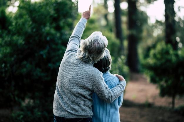 성숙한 노인 노인 커플 포옹과 숲에서 함께 야외 레저 활동을 즐길 수