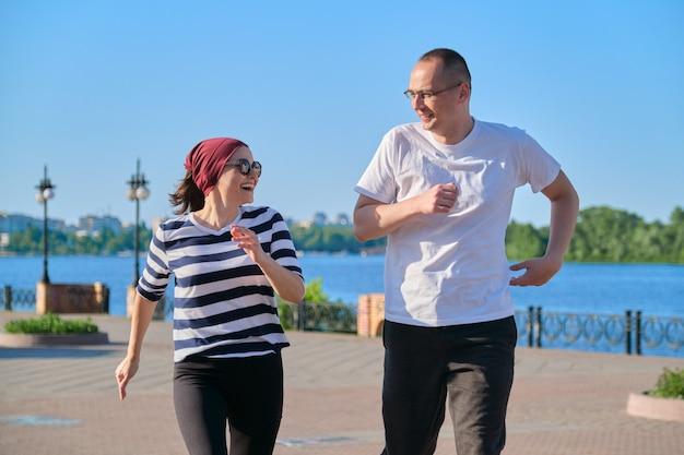 공원에서 달리는 중년 남녀 커플. 스포츠, 피트니스, 성숙한 사람들의 활동적인 건강한 라이프 스타일