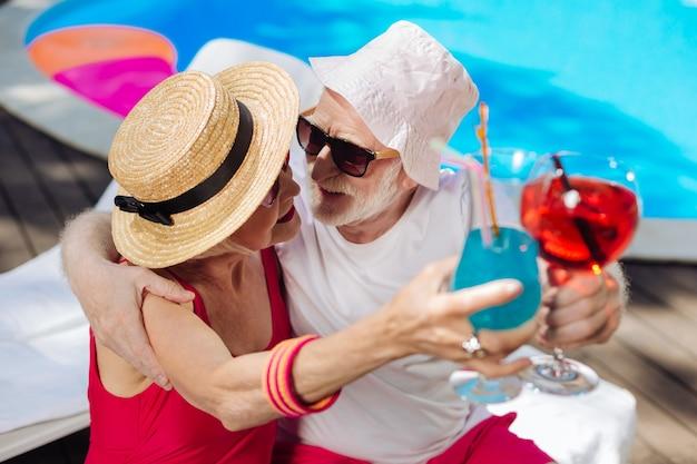 Пара современных стильных пенсионеров в ярких солнцезащитных очках пьет коктейли