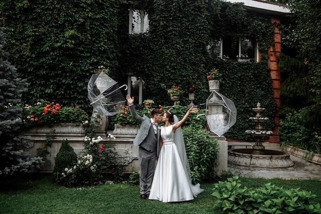 ツタと家の庭で結婚式の日に傘の下でキスする新婚新郎と新婦のカップル