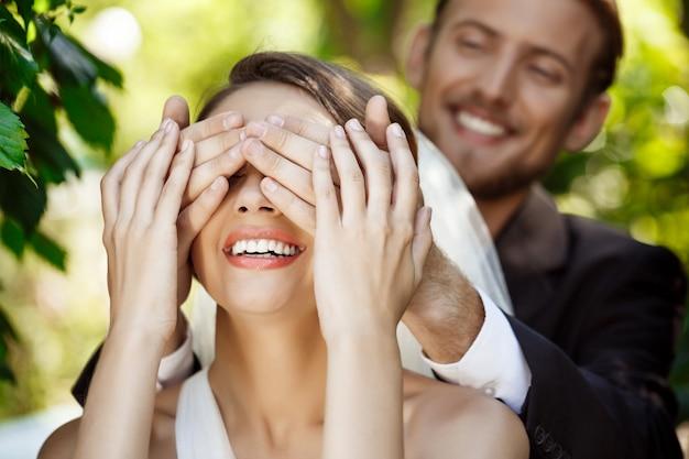 Пара молодоженов улыбается. жених закрывает глаза невесты руками.