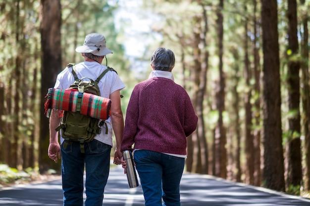 Пара пожилых пожилых путешественников идет посреди дороги с лесом вокруг и рюкзаком с одеялом на спине. любовь навсегда, партнерство и концепция естественного свободного образа жизни без возрастных ограничений