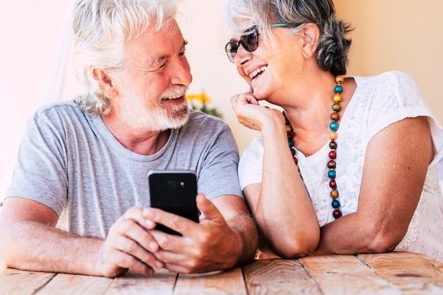 幸せな陽気な老人のカップルが愛をこめて一緒に笑みを浮かべて白人のシニア男性と女性