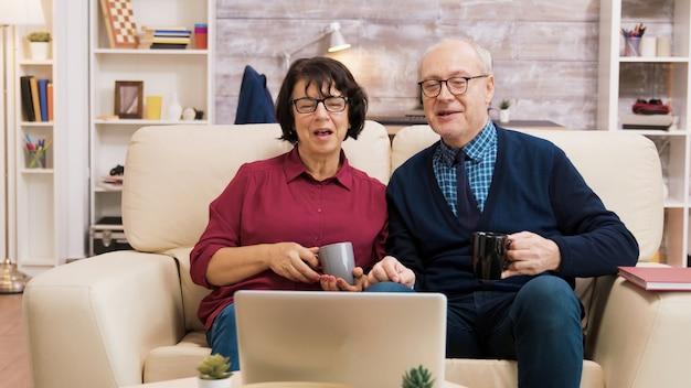 現代の技術を使用している老人のカップル。彼らはラップトップを使用してビデオ通話中です