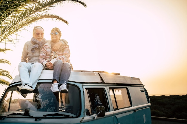 バンの屋根に一緒に座っている古いシニア旅行者のカップルは、愛と一緒に日没の時間を楽しんでいます-永遠にそして旅行者の引退した人々のための休暇の概念