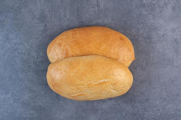 대리석 배경에 표시되는 타원형 빵의 커플. 고품질 사진 무료 사진