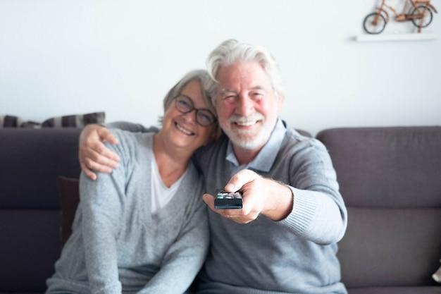 Пара пожилых пенсионеров смотрит и вместе смотрит телевизор дома, сидя на диване - два пожилых человека улыбаются, а мужчина переключает канал с помощью пульта дистанционного управления