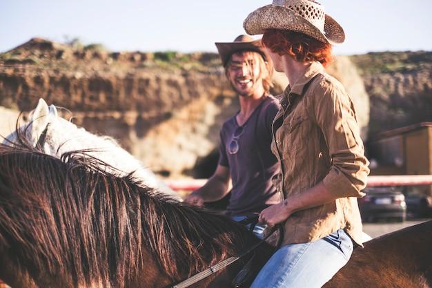 数人の人々と数頭の馬が田舎で一緒に余暇活動をしています。不在の現代的なライフスタイルと自然な生活と楽しみ方。男は女に微笑む。幸福