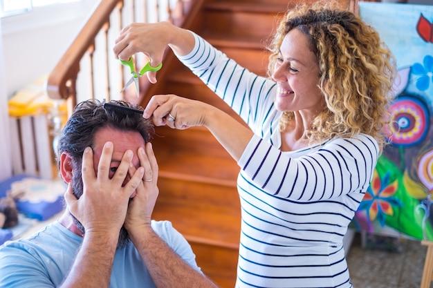 Пара людей, весело проводящих время вместе дома, наслаждаясь и играя с ножницами, подстригая волосы своего мужа - счастливая кудрявая женщина, стрижущая прическу мужчины