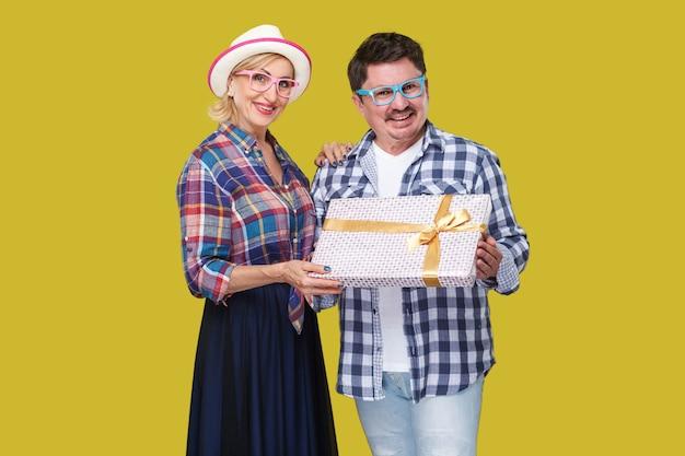 ポジティブな友達のカップル、プレゼントのギフトボックスを持って一緒に立っているカジュアルな市松模様のシャツを着た大人の男性と女性、歯を見せる笑顔と探しています。屋内、孤立した、スタジオショット、黄色の背景