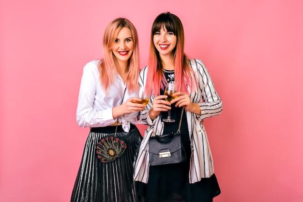 休日、エレガントな黒と白のイブニング衣装、トレンディなピンクのヘアスタイルを祝うかなりエレガントな親友の流行に敏感な女性のカップル、一緒に楽しい時間。