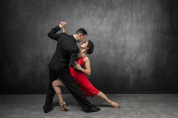 エレガントなスーツとドレスを着たプロのタンゴ ダンサーのカップルが、暗い背景に踊る動きで目を合わせてポーズをとる