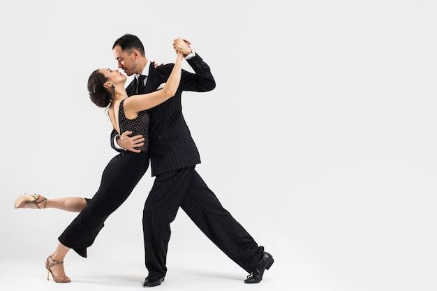 Пара профессиональных танцоров танго в элегантном костюме и платье позируют в танцевальном движении. привлекательный мужчина и женщина танцуют, глядя в глаза с любовью и страстью на белом фоне.