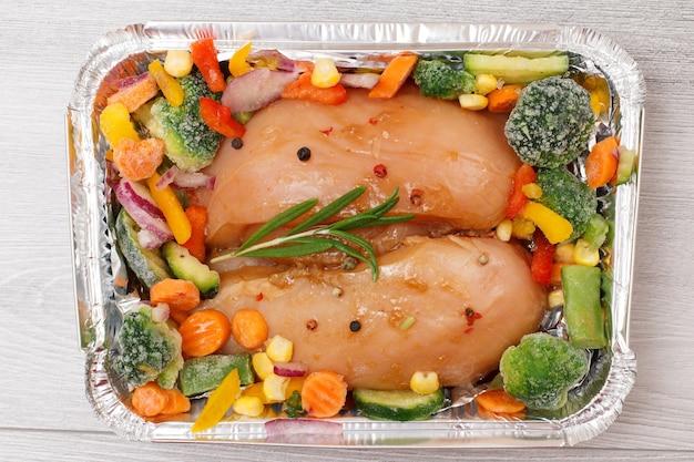 Пара сырых куриных грудок или филе с замороженными овощами в металлическом контейнере на деревянных фоне. вид сверху.