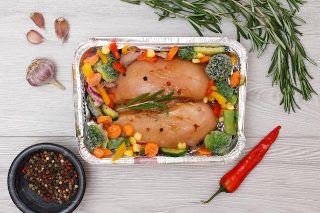 Пара сырых куриных грудок или филе с замороженными овощами в металлическом контейнере с чесноком, перцем чили, душистым перцем в стеклянной миске и розмарином на деревянном фоне. вид сверху.
