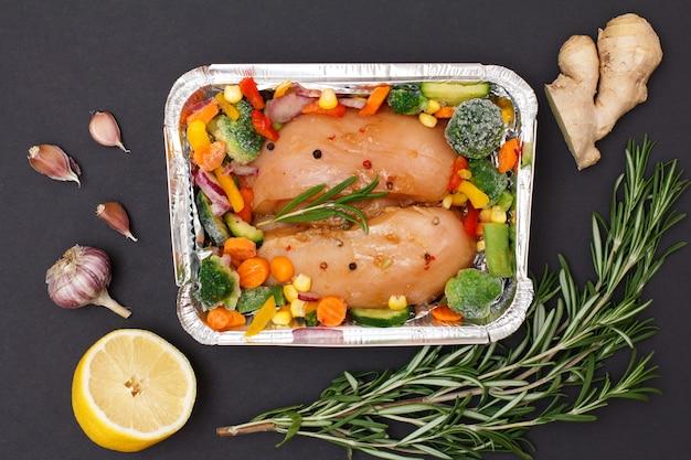 Пара сырых куриных грудок или филе с замороженными овощами в металлическом контейнере с чесноком, лимоном, луком, имбирем и розмарином на черном фоне. вид сверху.