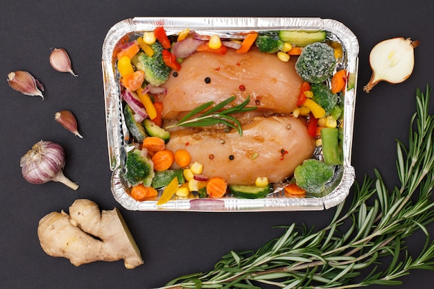 Пара сырых куриных грудок или филе с замороженными овощами в металлическом контейнере с имбирем, чесноком, луком и розмарином на черном фоне. вид сверху.