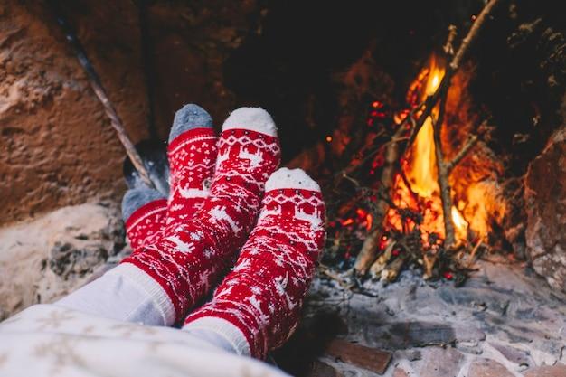 빨간 크리스마스 장식 양말 몇 켤레는 크리스마스 휴가철에 벽난로 앞에서 난방을 하고 있습니다. 로맨스와 사랑으로 축하하는 사람들의 개념. 남자와 여자는 샬레를 즐긴다