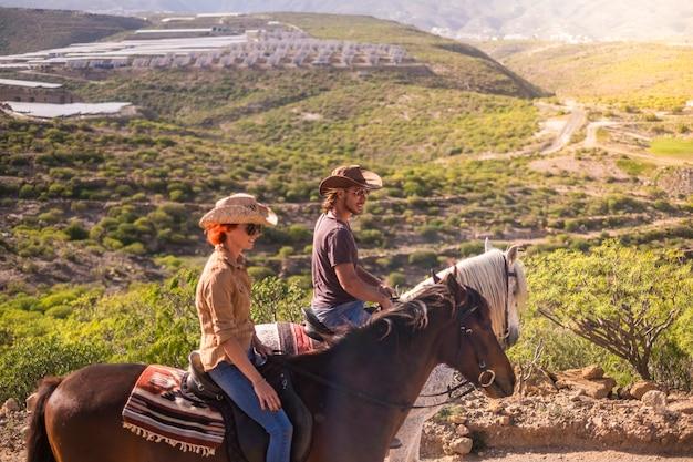 Пара всадников мужчина и женщина с коричневыми и белыми лошадьми идут и наслаждаются активным отдыхом на свежем воздухе во время экскурсии, путешествуя по горам. современный ковбой и без технологий