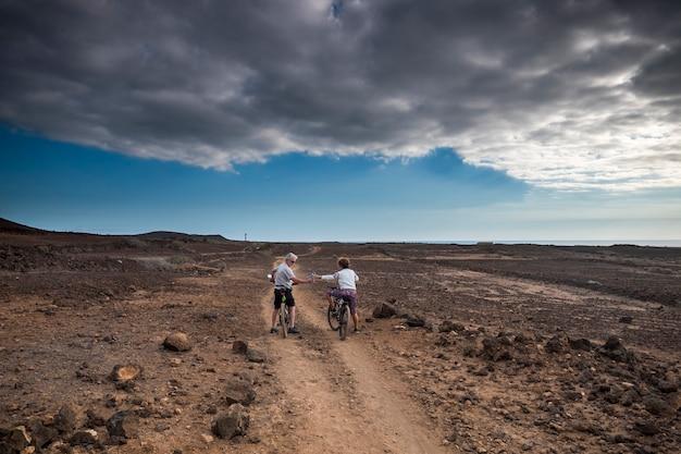 산악 자전거를 타는 라이더 두 명이 Ardi 사막 한가운데있는 길을 따라갑니다. 휴가를 즐기고 백인 사람들을위한 레저 스포츠 활동에서 모험을 발견하세요. 프리미엄 사진