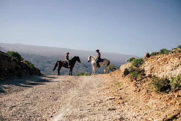 山の道で一緒にライダーと馬のカップル。別のライフスタイルの方法で世界を発見し、旅行します。自然を楽しみ、沈黙を感じてください。ウエスタンコンセプトシーン Premium写真