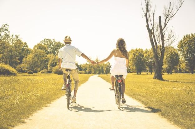 サイクリングのロマンチックな恋人のカップル-白人の人々-人、愛、自然、ライフスタイルのコンセプト
