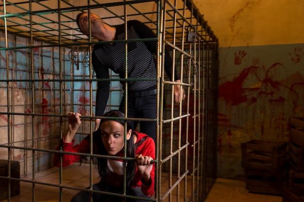 Пара напуганных жертв хэллоуина, заключенных в металлическую клетку с забрызганной кровью стеной позади них, выглядывают через решетку